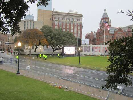 Dallas' Elm Street at Dealey Plaza is sectioned off for the upcoming ceremony in a few hours. A large banner with an image of JFK is being lifted into place where Main St. intersects with Dealey Plaza, in the background, while large video screens show videos and photos of Kennedy and his family accompanied by recorded soft piano music.  Photo: David Hendricks/San Antonio Express-News