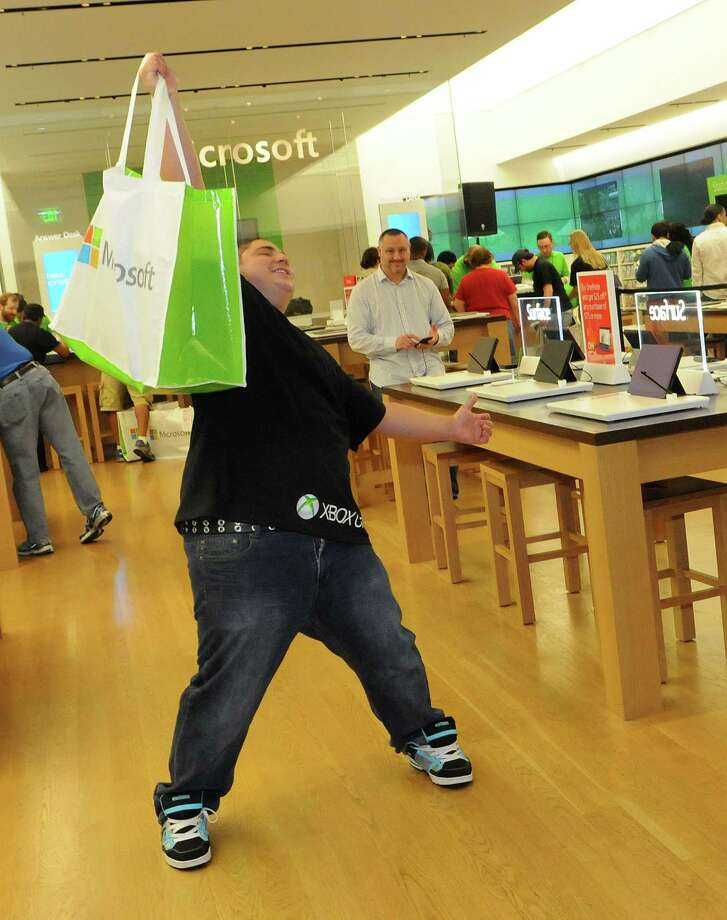 An excited fan shows off his new Xbox One after purchasing it at midnight from the Microsoft retail store at the Florida Mall on Friday in Orlando.  Photo: Gerardo Mora, Ap/getty / 2013 Gerardo Mora