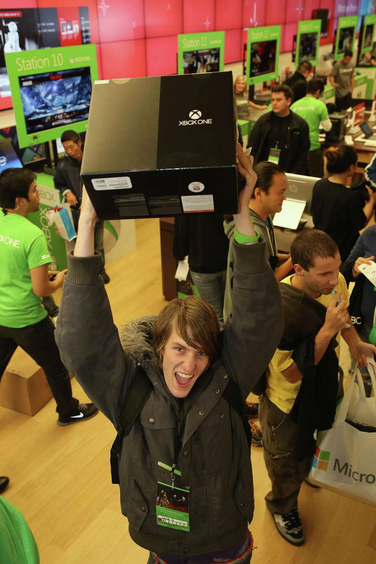 An excited fan shows off his new Xbox One after purchasing it at midnight from the Microsoft retail store in Fashion Valley Mall in San Diego on Friday.