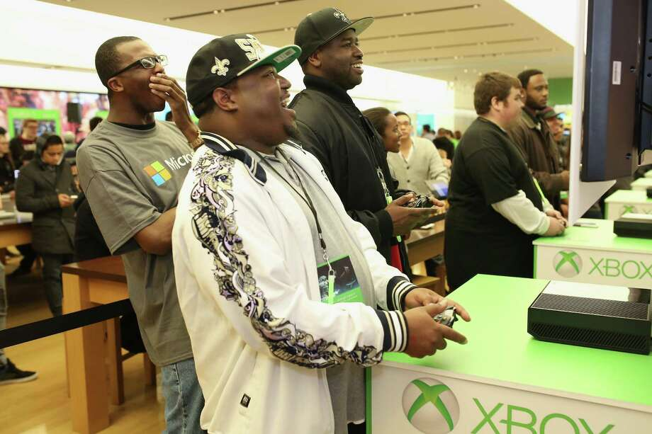 Fans compete in a gaming tournament at the Microsoft retail store at Fashion Valley Mall in San Diego on Friday for the chance to win up to $25,000 in prizes and a chance to participate in a final showdown at the Jacksonville, Fla. Microsoft Store opening, featuring a performance by Macklemore and Ryan Lewis. Tournament finalists will receive an Ultimate Xbox One Gaming House including all launch night titles in each of the six participating stores.  Photo: Robert Benson, Ap/getty / 2013 Getty Images