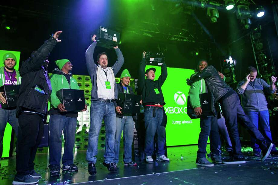 Some of the first 10 people to purchase the Microsoft Xbox One game system exalt in the moment at an event as they receive their equipment in New York Friday.  Xbox One is a new all-in-one games and entertainment system from Microsoft.  Photo: Craig Ruttle, Ap/getty / FR61802 AP