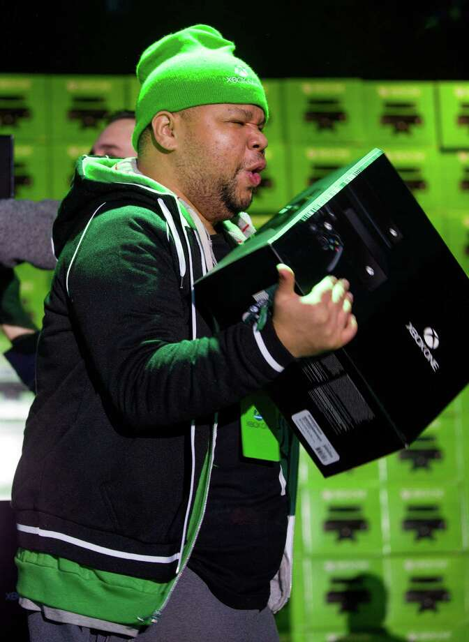 Hanoi Delosangeles of New York, the first person to buy the Microsoft Xbox One game system, exalts in the moment at an event in New York on Friday. Photo: Craig Ruttle, Ap/getty / FR61802 AP