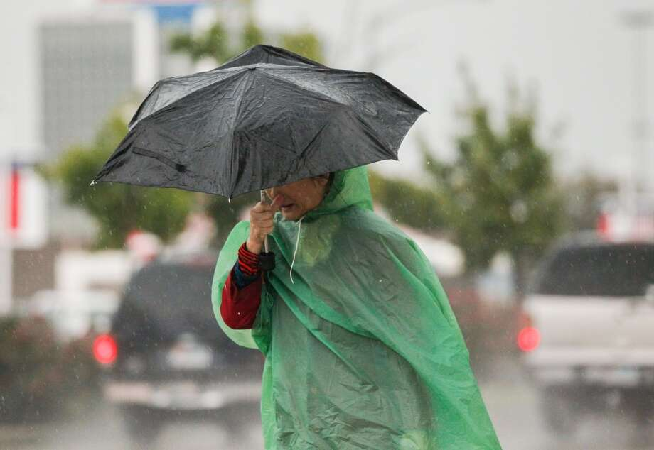 Pedestrians walk through the rain on Fondren Friday, Nov. 22, 2013. Photo: Johnny Hanson, Houston Chronicle