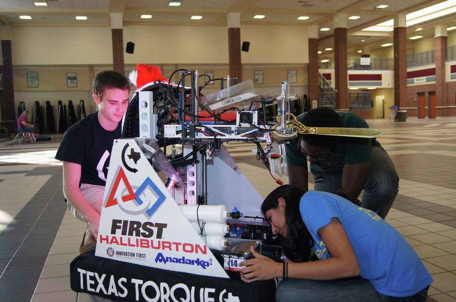 Members of the Conroe ISD Texas Torque Robotics team, Bradley Holloway, from left, Vaishu Kishore and Keene Chin work on the robot that will cut the ribbon during the opening ceremony for the Macy's Thanksgiving Day parade on Nov. 28 in New York City. Photo: CISD Courtesy