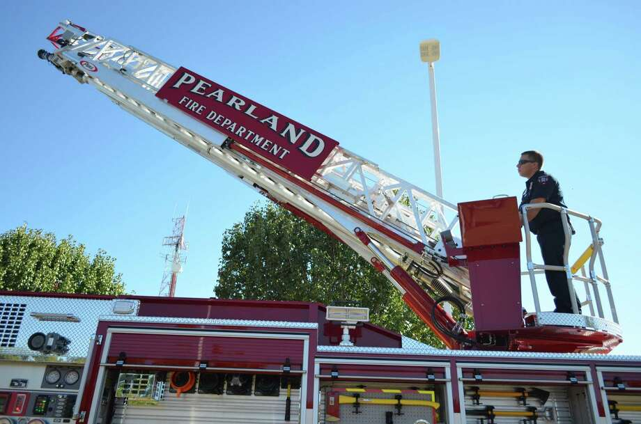 Jason Strelow, driver/operator of Pearland's newest ladder truck, showcases some of the truck's features during a Nov. 2 celebration for the new Pearland Fire and EMS administration building. Photo: Derek Salyer, Freelance / Freelance