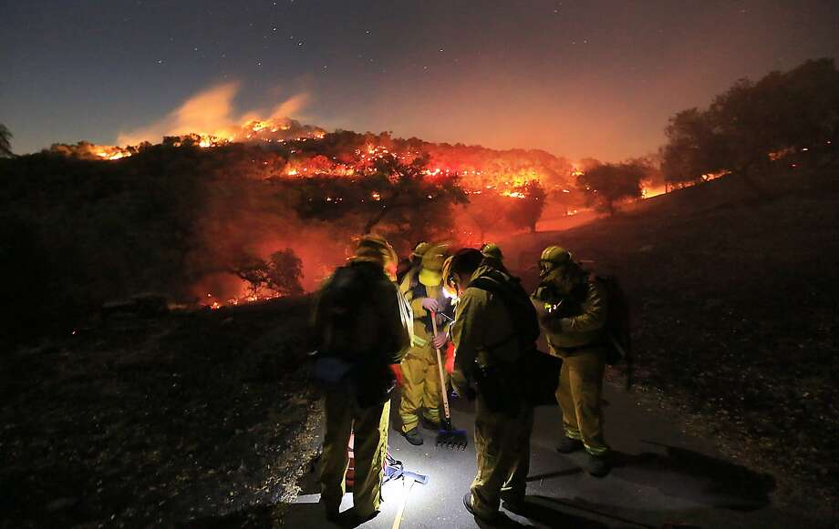 Firefighters from Schell Vista of Sonoma County and Santa Clara County Cal Fire prepare to put out hotspots on a fire in the hills of Soda Canyon above Napa, Calif., Friday, Nov. 23, 2013.  The fire grew to over 300 acres by daybreak, fanned by high winds. (AP Photo/Santa Rosa Press Democrat, Kent Porter) Photo: Kent Porter, Associated Press
