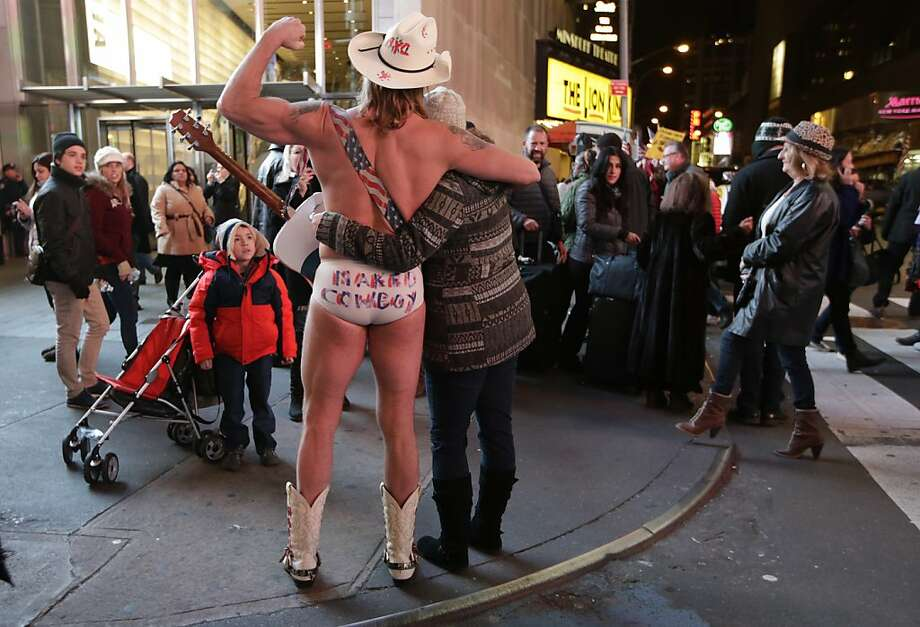 Shriveling in the cold: While the rest of New York bundles up in parkas and topcoats, the Naked Cowboy braves the autumn chill in nothing but his signature tighty-whities, hat and boots. Photo: Kathy Willens, Associated Press