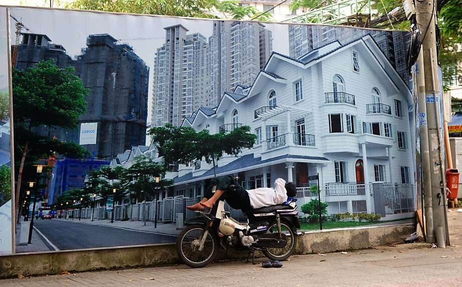 To have and have not in communist Vietnam: A motorbike taxi driver naps in front of a billboard advertising upscale real estate in downtown Ho Chi Minh City. The newly built luxury shopping mails and residential buildings in Vietnam's largest city underscore the gap between rich and poor. Photo: Hoang Dinh Nam, AFP/Getty Images