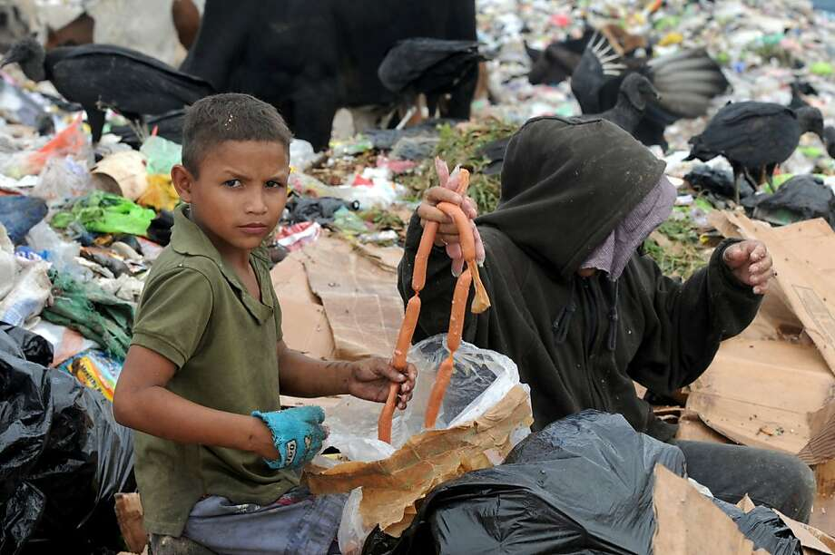 Sausage salvaged: A mother and son scavenge for food at the municipal rubbish dump north of Tegucigalpa, Honduras. Photo: Orlando Sierra, AFP/Getty Images