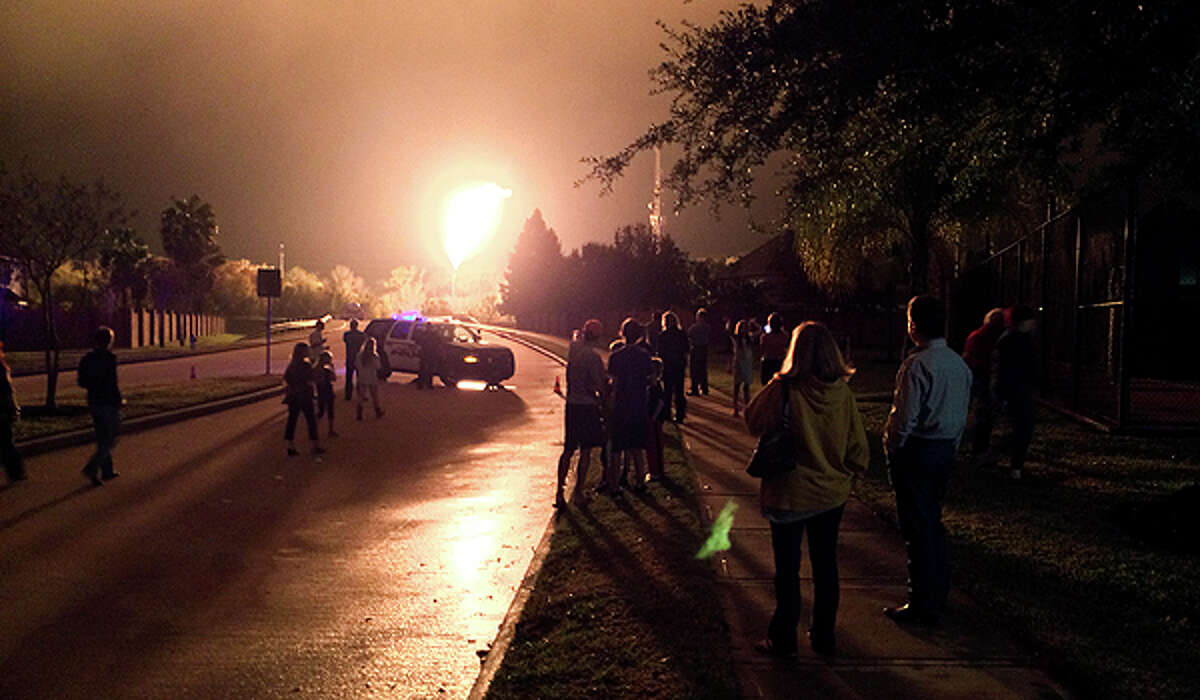 Sugar Land residents look on as Atmos Energy conducts a controlled burn as part of maintenance for a gas line Thursday night, Nov. 21, 2013.