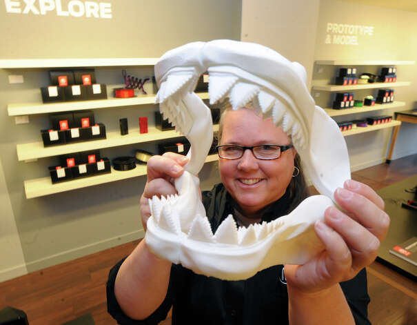 MakerBot Manager of Retail Operations, Jackie Johnson, displays a plastic model of the jaws of a Great White Shark that were made by a MakerBot 3-D printer during the grand opening of the MakerBot Store-Greenwich at 72 Greenwich Ave., Friday, Nov. 22, 2013. MakerBot sells top-of-the-line 3D printers and accessories to print 3-D objects. Jenny Lawton, former owner of Just Books in Old Greenwich, is the president of MakerBot. Photo: Bob Luckey / Greenwich Time