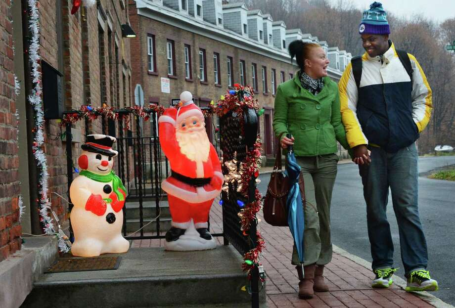 LaMonica Bacon, 17, left, and Leroy Dalton, 16, both of Cohoes, walk past some early Christmas decorations along Olmstead Street Friday Nov. 22, 2013, in Cohoes, NY.  (John Carl D'Annibale / Times Union) Photo: John Carl D'Annibale