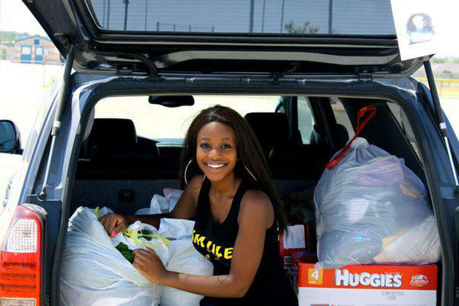 Alexis Harris, founder of the nonprofit SMIILE, an acronym for students making impacts in lives everywhere, collects garments from a clothing drive for the needy. Photo: Courtesy Photo