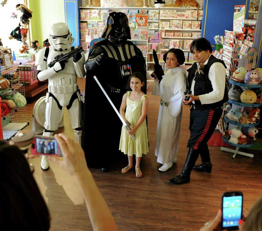 "Kaliana Gartoles, 9, has a photo taken with ""Star Wars"" movie characters at Stone Oak Learning Express in August. The event helped gather food for the needy. Photo: John Albright / For North Central News"