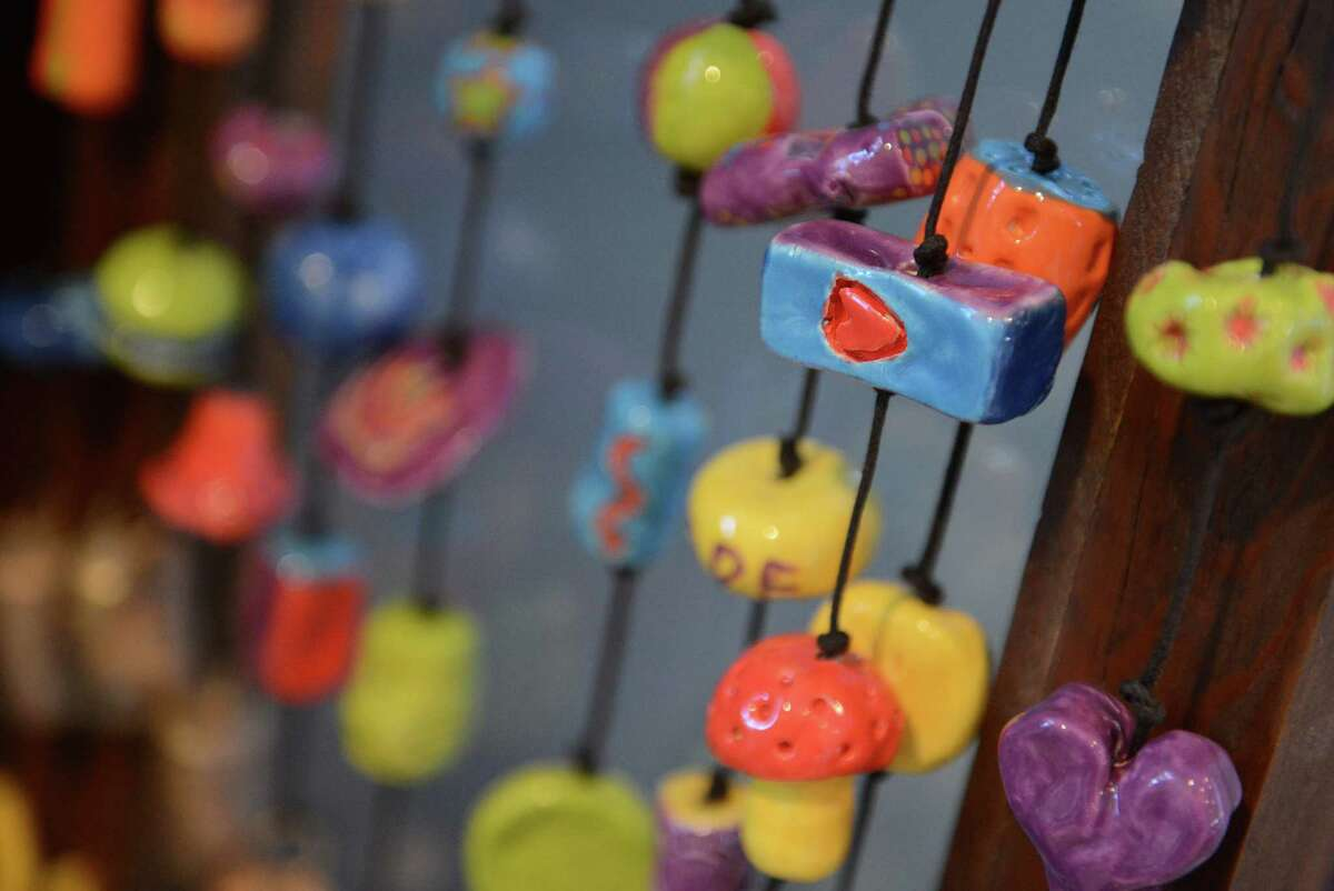 A painted heart, and other colorful ceramic decorations adorn the strings of Ben's Bells at Ben's Bells Studio in Newtown, Conn. on Wednesday, Nov. 20, 2013. Ben's Bells are colorful, ceramic pieces of art hung in public places with tags instructing the finder to take the bell home with them and remember to be kind. The project was started by a family in Arizona after losing their child, Ben, before his third birthday. The studio in Newtown is the only one outside of Arizona.