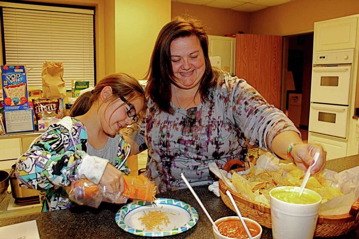 Parkway United Methodist Church volunteers Elizabeth Charkalis, 10, and her mother, Debra Charkalis, pour grated cheese into a bowl and stir cheese dip in preparation for a meal for Family Promise families. The church at 5801 New Territory is in Sugar Land.
