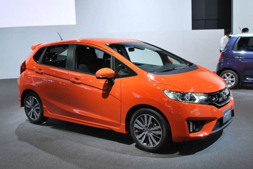 The honda fit this tiny orange car manages to squeeze in for Orange honda fit