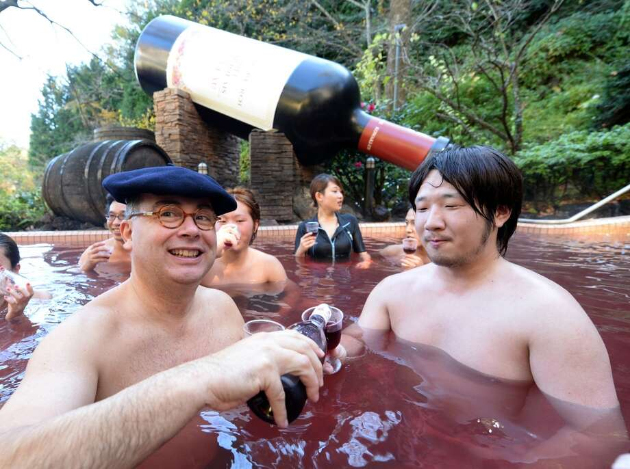 Bourgogne wine maker Laboure-Roi vice president Thibault Garin (L) offers the company's 2013 Beaujolais Nouveau wine to the guest in the wine spa at the Hakone Yunessun spa resort facilities in Hakone. Photo: Toshifumi Kitamura, AFP/Getty Images