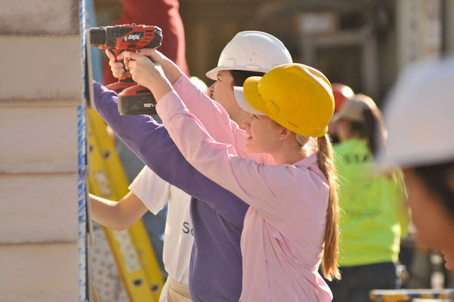 Caroline Miller uses a drill while building a Habitat for Humanity home. She was one of more than 250 volunteers working on nine Habitat homes in the Morning Star Terrace project early this year. Photo: Express-News File Photo