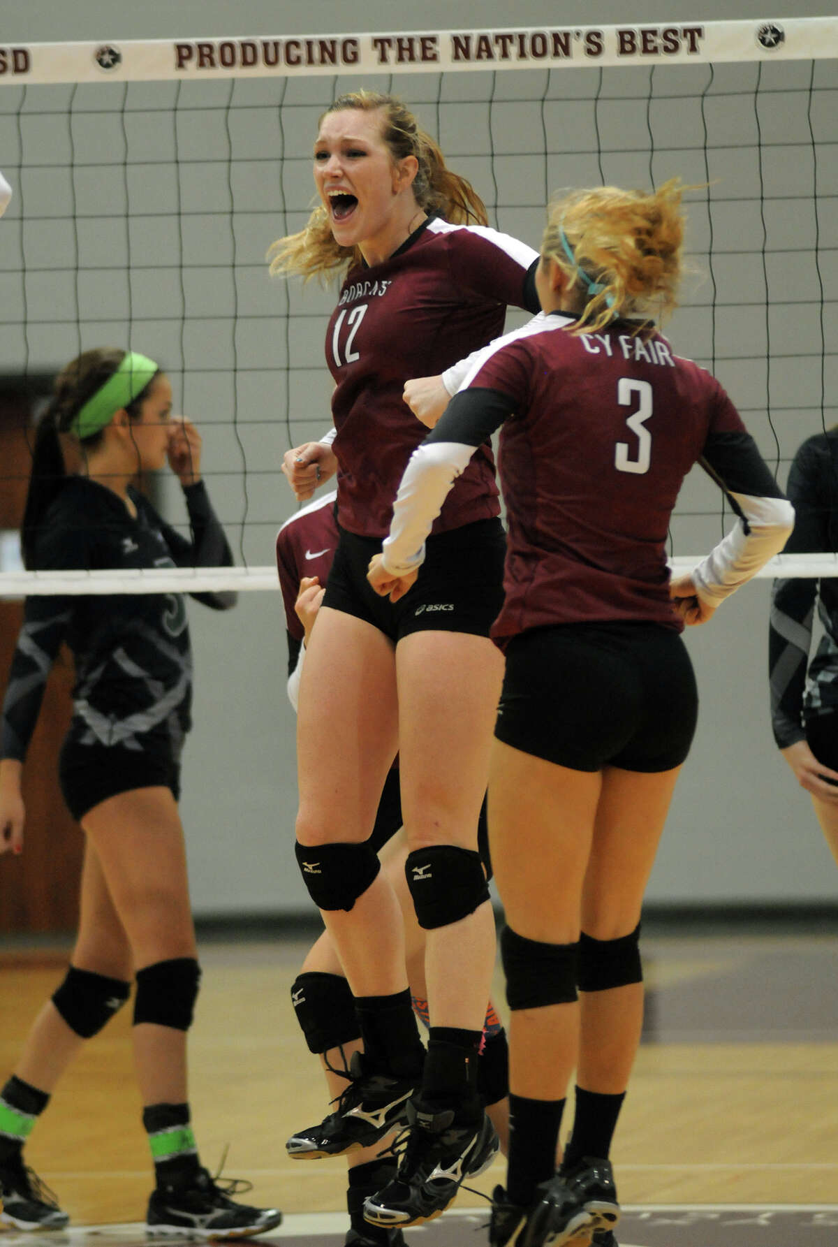 Cy-Fair senior setter Keely Hayes (#12) and senior defensive specialist Emily Rogers (#3) celebrate a Lady Bobcat point against Clear Falls during their Region III-5A regional final volleyball playoff at the Campbell Center on Saturday.