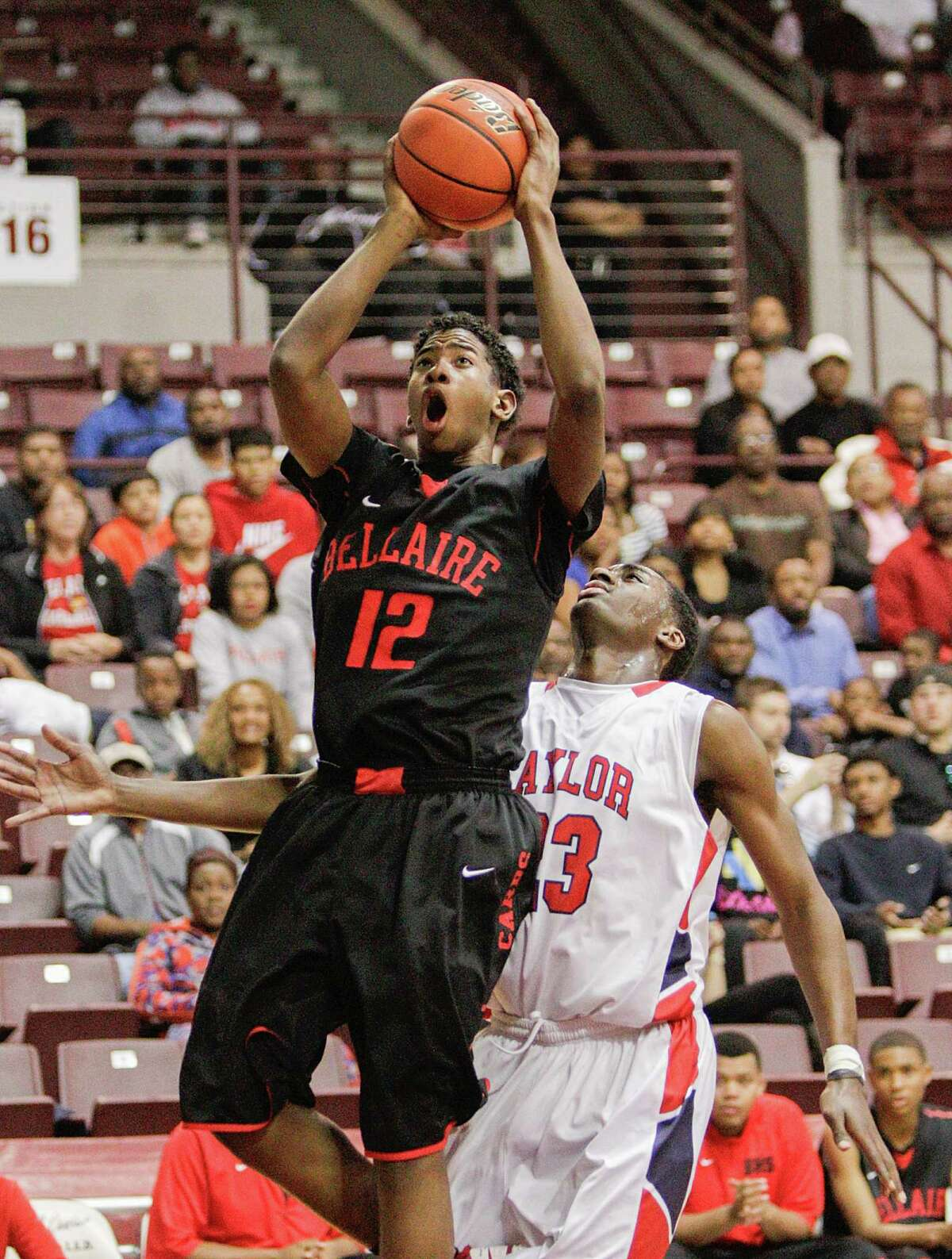 Bellaire's Christian James shoots past Alief Taylor's Keenen Brown #23 during a Class 5A Region III quarterfinal basketball game Tuesday, February 26, 2013 at the M.O. Campbell Center in Houston. (Bob Levey/For The Houston Chronicle)