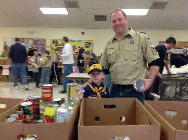 Members of Preceptor Beta Psi, a Clifton Park Chapter of Beta Sigma Phi International Sorority volunteered earlier this month at the Jonesville Food Pantry in the United Methodist Church in Jonesville. Boy Scouts collected non-perishable foods from local neighborhoods and delivered them to the pantry. Here, Scout leader Rob Croteau and his son, Nate, Troop 6 - Pack 42 in Clifton Park, help out. The chapter also donates a Thanksgiving food basket to the Saratoga Womens Domestic Violence & Crisis Services.(Priscilla Wyman)