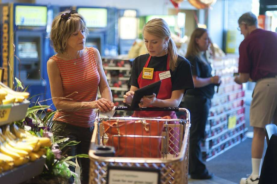 Safeway employee Whitney Swanson enrolls Joy Combs in the chain's Just For U loyalty program, which offers personalized pricing and coupons, in Denver. Photo: Kevin Moloney, New York Times
