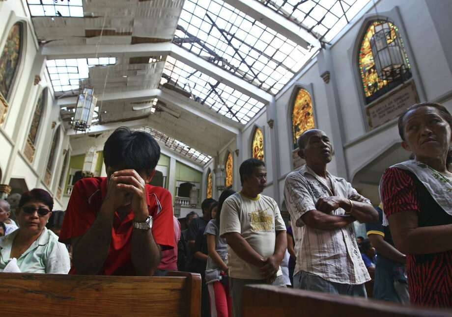 A Filipino man prays during Mass at Santo Niño Church, which was damaged by Typhoon Haiyan in Tacloban, Philippines. Catholic organizations in the Philippines have started relief efforts for survivors of the typhoon. Photo: Dita Alangkara / Associated Press
