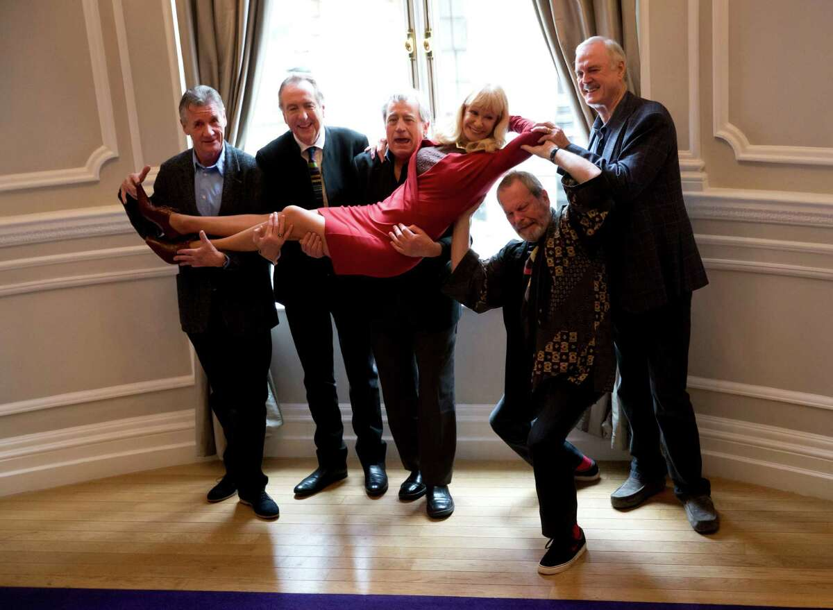The surviving members of the Monty Python comedy group, from left, Michael Palin, Eric Idle, Terry Jones, Terry Gilliam, and John Cleese pick up their co-star Carol Cleveland whilst posing for photographers during a photocall to promote a reunion stage show they are going to perform together, at a hotel in London, Thursday, Nov. 21, 2013. The group had its first big success with the Monty Python's Flying Circus TV show, which ran from 1969 until 1974, winning fans around the world with its bizarre sketches. (AP Photo/Matt Dunham)