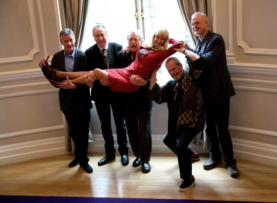 The surviving members of the Monty Python comedy group, from left, Michael Palin, Eric Idle, Terry Jones, Terry Gilliam, and John Cleese pick up their co-star Carol Cleveland whilst posing for photographers during a photocall to promote a reunion stage show they are going to perform together, at a hotel in London, Thursday, Nov. 21, 2013.  The group had its first big success with the Monty Python's Flying Circus TV show, which ran from 1969 until 1974, winning fans around the world with its bizarre sketches. (AP Photo/Matt Dunham) Photo: Matt Dunham, STF / AP