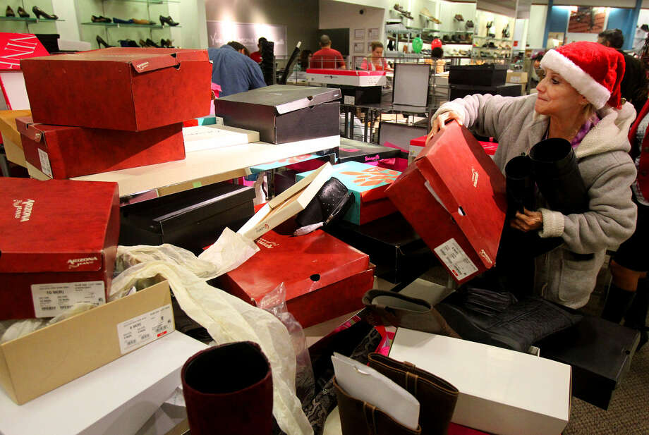 Rose Pena sifts through a pile of shoe boxes looking for a boot that matches the one she was hoping to purchase at J.C. Penny at North Star Mall last year on Black Friday. Photo: Express-News File Photo