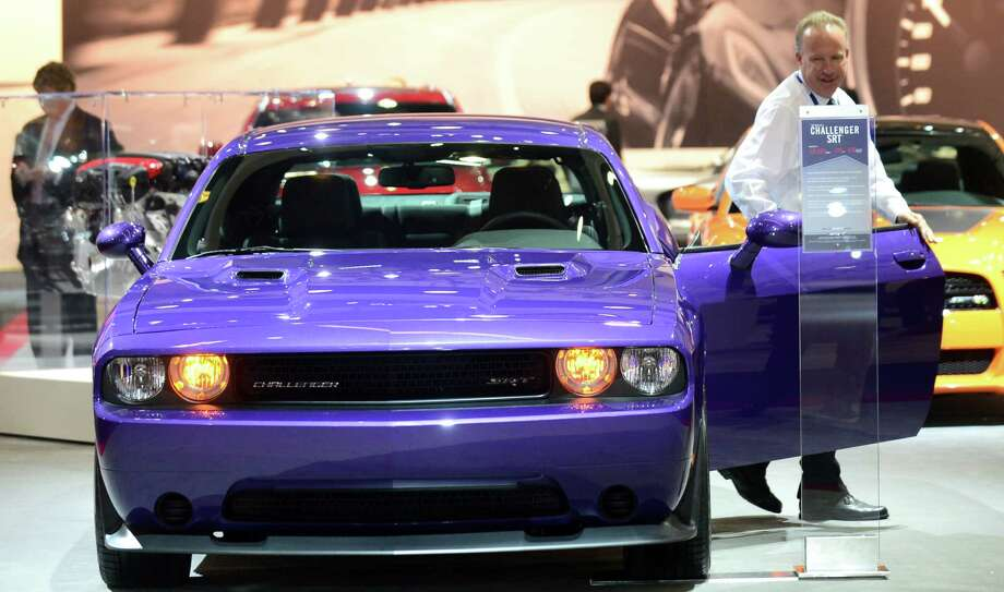 A man steps out of a 2014 Challenger SRT from Dodge displayed on November 21, 2013 at the LA Auto Show in Los Angeles, California. Photo: FREDERIC J. BROWN, Getty Images / 2013 AFP