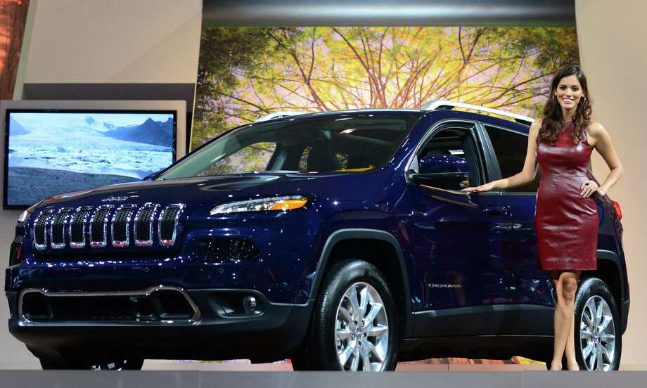 A spokesmodel poses beside a 2014 Jeep Cherokee displayed on November 21, 2013 at the LA Auto Show in Los Angeles, California. Photo: FREDERIC J. BROWN, Getty Images / 2013 AFP