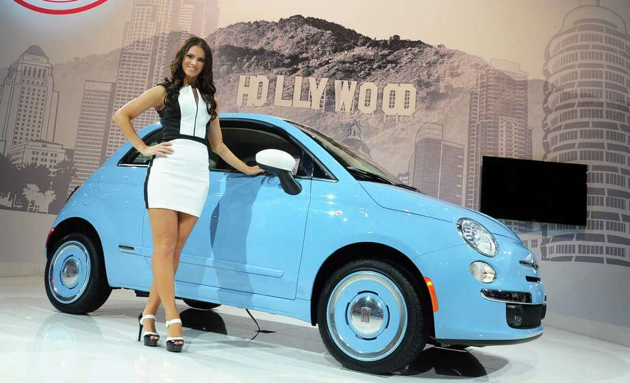 A spokesmodel poses beside the 2014 Fiat 500 1957, displayed on November 21, 2013 at the LA Auto Show in Los Angeles, California. Photo: FREDERIC J. BROWN, Getty Images / 2013 AFP