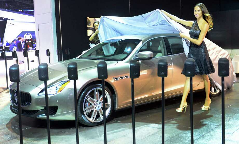 Spokesmodels cover up the 2014 Maserati Quattroporte Ermenegildo Zegna edition displayed on November 20, 2013 during media previews at the LA Auto Show in Los Angeles, California. Photo: FREDERIC J. BROWN, Getty Images / 2013 AFP