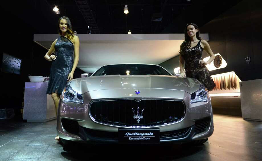 Spokesmodels pose beside the 2014 Maserati Quattroporte Ermenegildo Zegna edition displayed on November 20, 2013 during media previews at the LA Auto Show in Los Angeles, California. Photo: FREDERIC J. BROWN, Getty Images / 2013 AFP