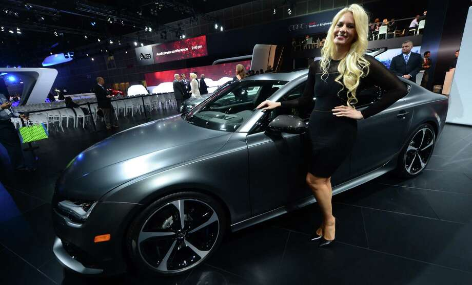 A spokesmodel poses beside an Audi RS7 displayed on November 20, 2013 during media previews at the LA Auto Show in Los Angeles, California. Photo: FREDERIC J. BROWN, Getty Images / 2013 AFP