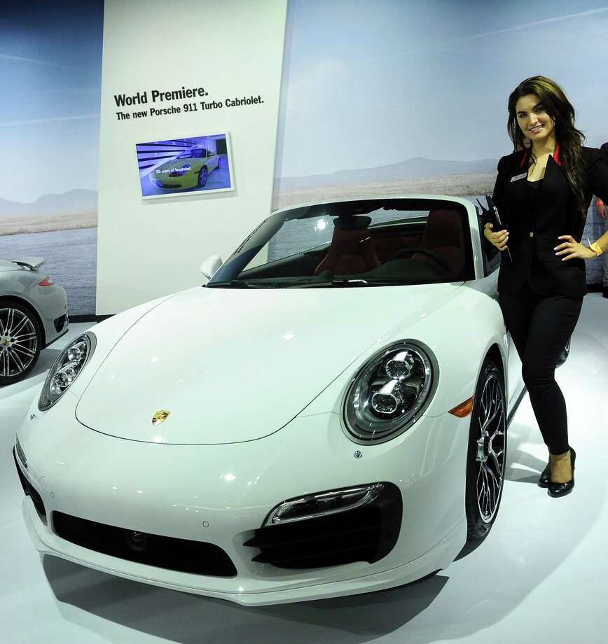 A spokesmodel poses beside the new Porsche 911 Turbo Cabriolet displayed on November 20, 2013 at the LA Auto Show in Los Angeles, California. Photo: FREDERIC J. BROWN, Getty Images / 2013 AFP