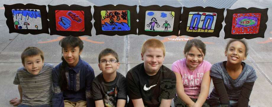 Harrison Steed, 7, from left, Sophia Tran, 10, Jackson Hensley, 8, Kevin Durney, 11, Maria Gamron, 10, and Vanessa Ndahiro, 11, pose with their Thanksgiving art projects shown through a window at Lowery Elementary School. Every student in the school participated in the art project. Photo: Melissa Phillip, Staff / © 2013  Houston Chronicle