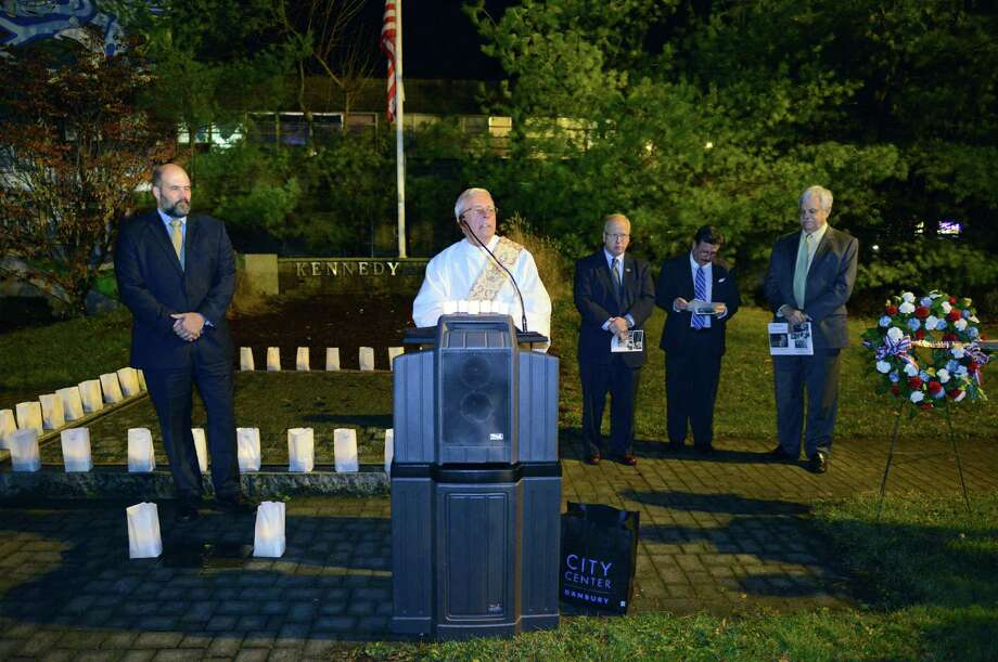 Deacon Richard Kovacs, center, speaks at the John F. Kennedy remembrance ceremony, presented by CityCenter Danbury and the Danbury Democratic Town Committee, at Kennedy Park in Danbury, Conn. on Friday, Nov. 22, 2013.  The ceremony, on the 50th anniversary of his assassination, included the lighting of luminaries surrounding the park's fountain, the laying of a wreath by Mayor Mark Boughton and former Mayor Gene Eriquez, and speeches of remembrance from area officials. Photo: Tyler Sizemore / The News-Times