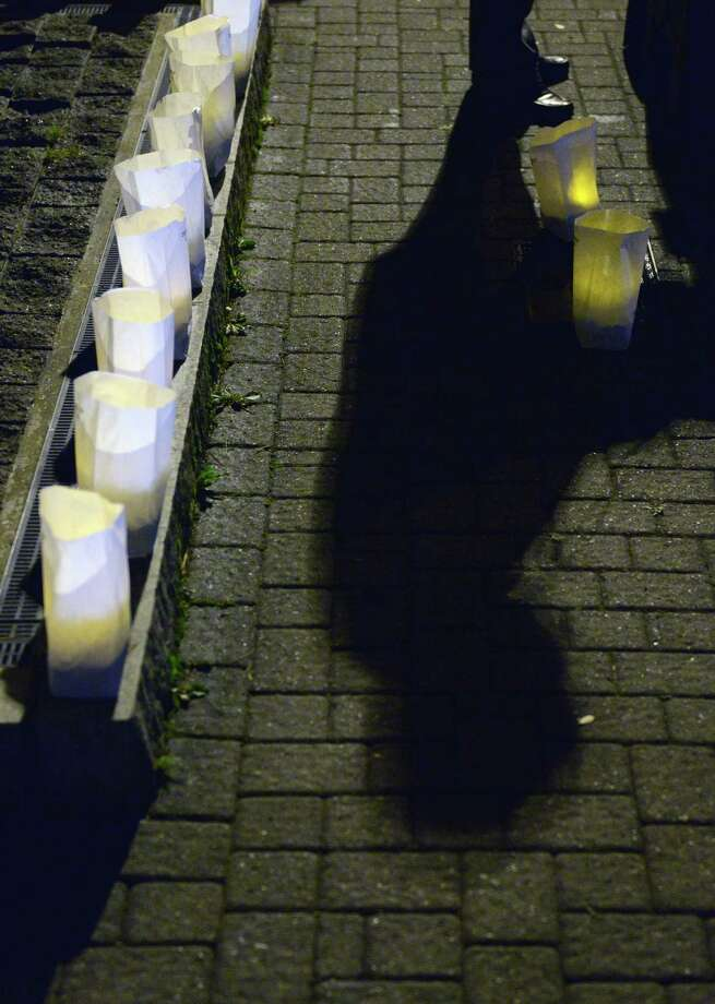 State Rep. Robert Godfrey speaks as luminaries line the fountain at Kennedy Park for the John F. Kennedy remembrance ceremony, presented by CityCenter Danbury and the Danbury Democratic Town Committee, in Danbury, Conn. on Friday, Nov. 22, 2013.  The ceremony, on the 50th anniversary of his assassination, included the lighting of luminaries surrounding the park's fountain, the laying of a wreath by Mayor Mark Boughton and former Mayor Gene Eriquez, and speeches of remembrance from area officials. Photo: Tyler Sizemore / The News-Times