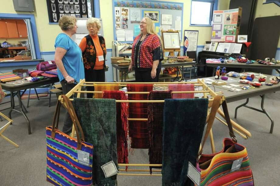 United Methodist Women, left to right, Sandi Donahue, Mary Herrivk and Amanda Smith-Lucier amid the Guatemalan crafts for sale during the Mayan Hands Fair Trade sale at the Alplaus United Methodist Church on Friday Nov. 22, 2013 in Alplaus, N.Y. The sale continues Saturday Nov. 23 from 10:00am to 3:00 pm. (Michael P. Farrell/Times Union) Photo: Michael P. Farrell / 00024701A