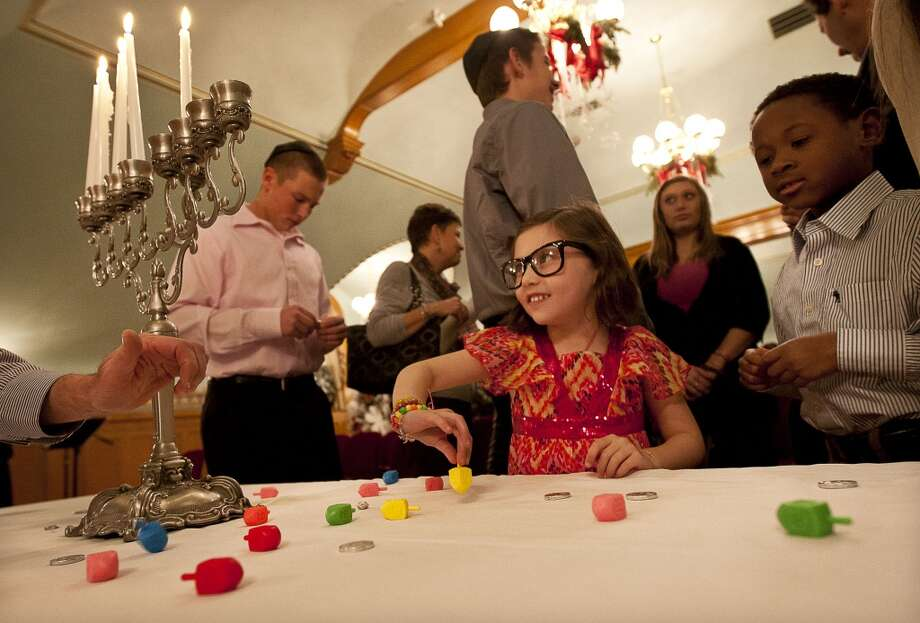 6. Play dreidel. After the table has been cleared, sip some sweet Manischewitz wine as a nightcap while spinning the dreidel and playing the gambling game. Photo: Ben Brewer, Associated Press