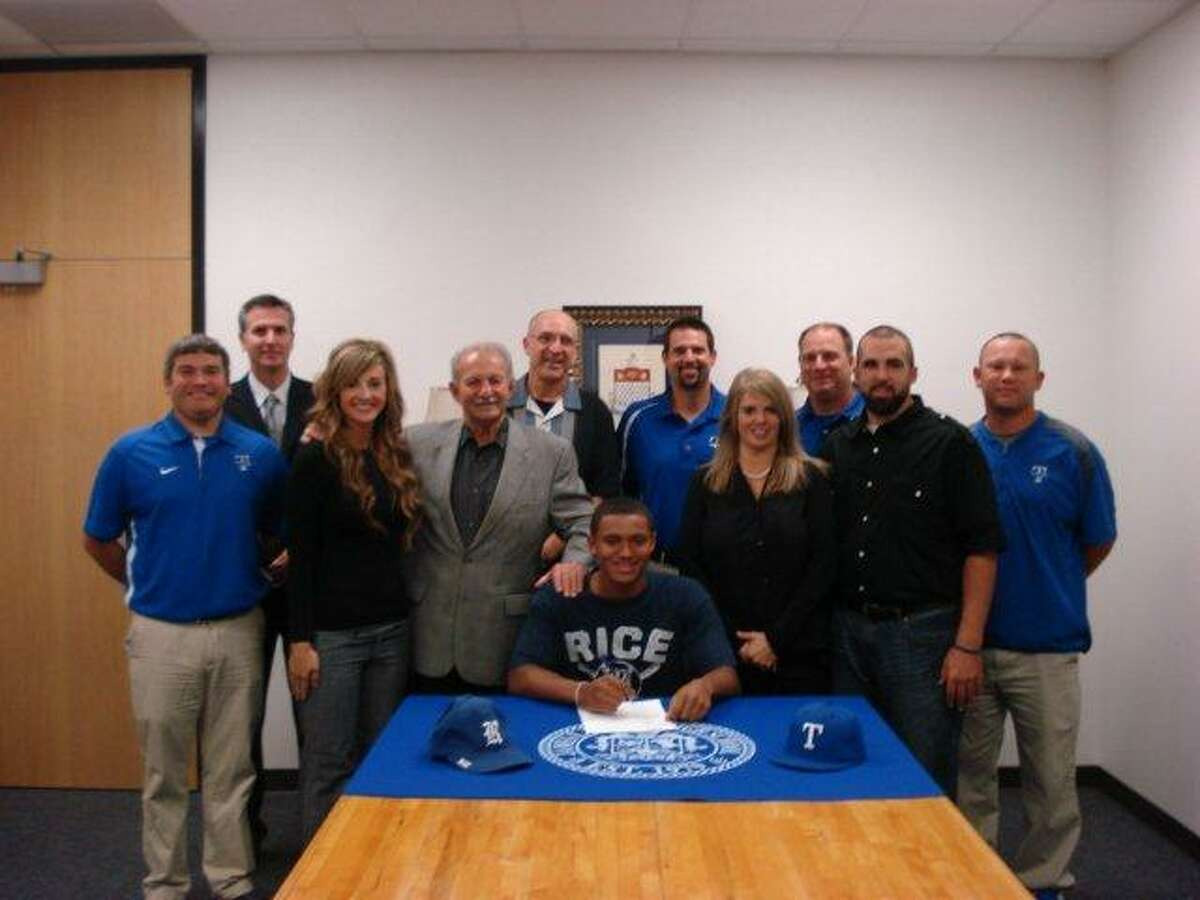 Dane Myers signs his letter of intent with family, coaches and school officials present.