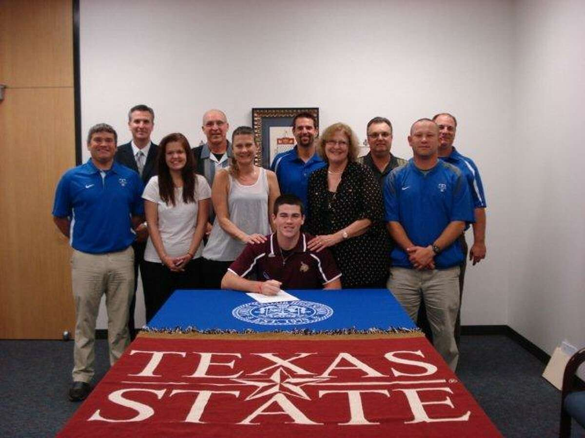 Dylan Paul, center, signs his letter of intent in front of his family, coaches and school personnel.