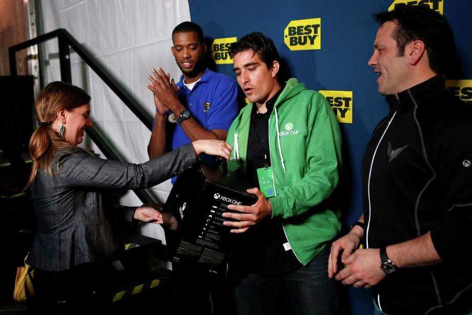 Carlos Anthony, second right, reacts as he receives the first Xbox One video games console to be sold during the Microsoft Corp. midnight launch event in Los Angeles, California, U.S., on Friday, Nov. 22, 2013. The Xbox One console incorporates software and systems developed throughout the rest of Microsoft and is the first big test of what the company calls its One Microsoft strategy. Photographer: Patrick T. Fallon/Bloomberg *** Local Caption *** Carlos Anthony Photo: Patrick T. Fallon, Courtesy / Copyright 2013 Bloomberg Finance LP, All Rights Reserved.