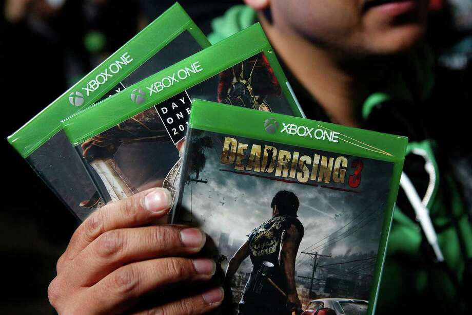 A customer poses with three new Xbox One video games after purchasing them during the Microsoft Corp. midnight launch event in Los Angeles, California, U.S., on Friday, Nov. 22, 2013. The Xbox One console incorporates software and systems developed throughout the rest of Microsoft and is the first big test of what the company calls its One Microsoft strategy. Photographer: Patrick T. Fallon/Bloomberg Photo: Patrick T. Fallon, Courtesy / Copyright 2013 Bloomberg Finance LP, All Rights Reserved.