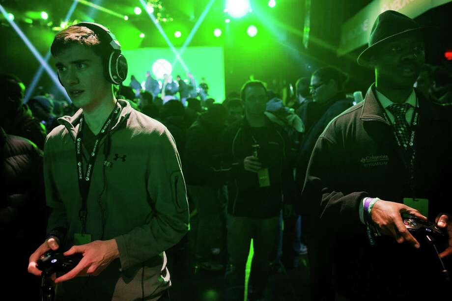 Michael Sisk, 21, left, and Mark Callender, try out the new Xbox game console during the Microsoft Corp. midnight launch event in New York, U.S., on Thursday, Nov. 21, 2013. The Xbox One console incorporates software and systems developed throughout the rest of Microsoft and is the first big test of what the company calls its One Microsoft strategy. Photographer: Victor J. Blue/Bloomberg Photo: Victor J. Blue, Courtesy / © 2013 Bloomberg Finance LP