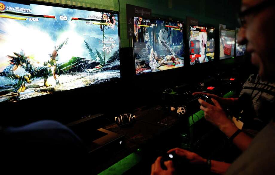 Visitors play on Xbox One video games consoles during the Microsoft Corp. midnight launch event in Los Angeles, California, U.S., on Thursday, Nov. 21, 2013. The Xbox One console incorporates software and systems developed throughout the rest of Microsoft and is the first big test of what the company calls its One Microsoft strategy. Photographer: Patrick T. Fallon/Bloomberg Photo: Patrick T. Fallon, Courtesy / © 2013 Bloomberg Finance LP