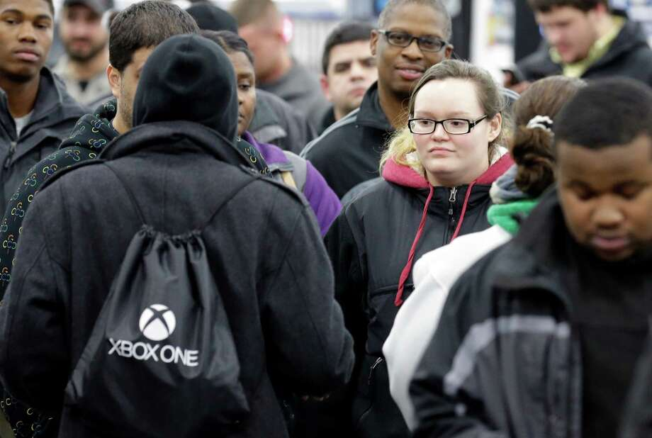 Customers line up to get their hands on the newest XBox One that goes on sale at midnight at a Best Buy on Friday, Nov. 22, 2013., in Evanston, Ill.  Microsoft is billing the Xbox One, which includes an updated Kinect motion sensor, as an all-in-one entertainment system rather than just a gaming console.  (AP Photo/Nam Y. Huh) Photo: Nam Y. Huh, Courtesy / AP